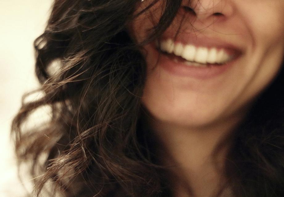 femme sourire brune cheveux bouclés