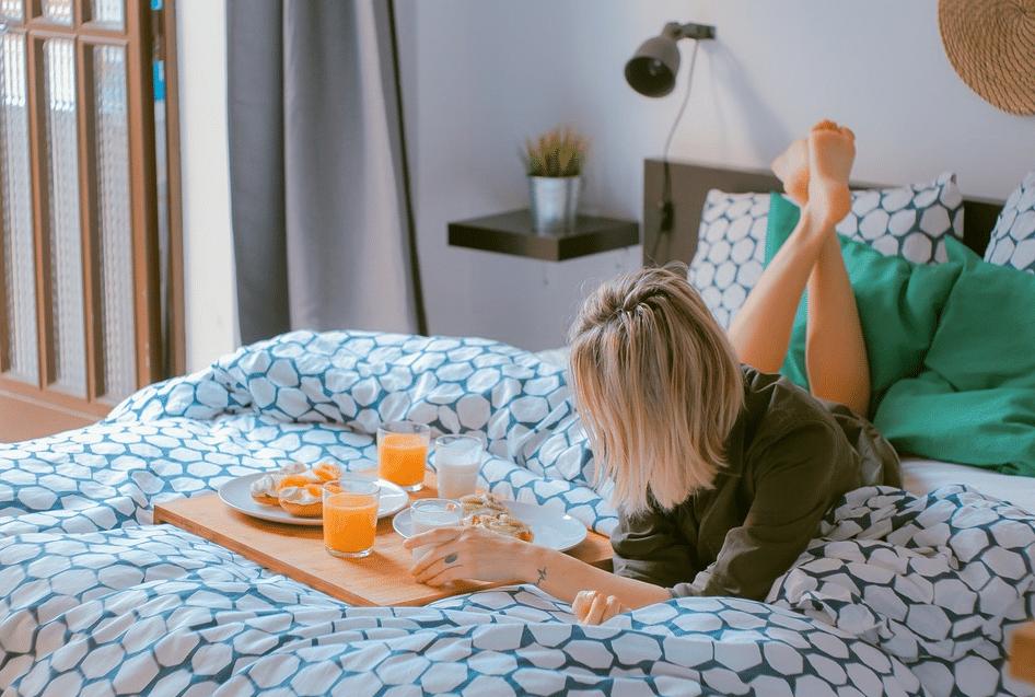 femme petit-déjeuner lit matin jus d'orange