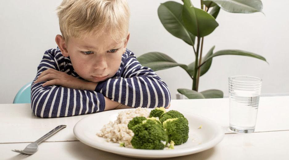 garçon boude ses légumes