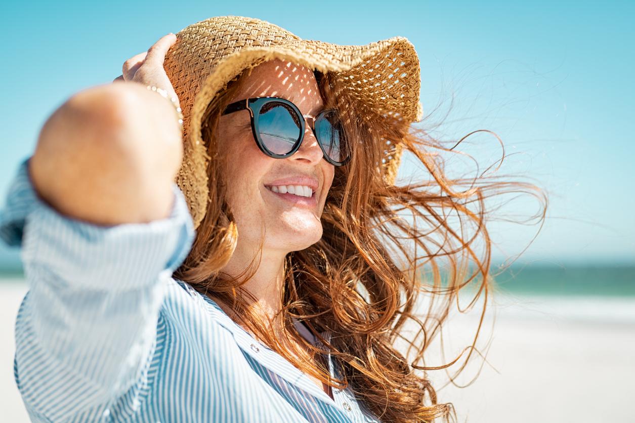 femme chapeau été plage lunettes de soleil cheveux dans le vent